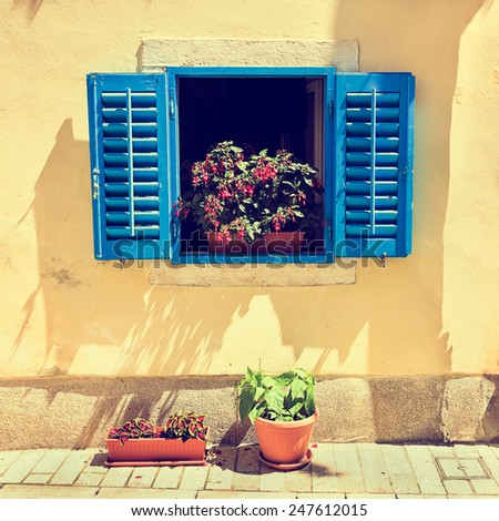Retro Blue Window with Open Shutters in Mediterranean Style with Flowers in Pot. Cute Toned and Filtered Instagram Styled Photo. - stock photo
