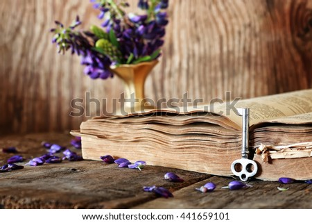 retro book on wooden table key - stock photo