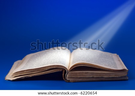 retro book with light rays on blue background