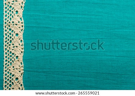 Retro border for invitations celebration. Vintage white lace over green blue textile background. - stock photo