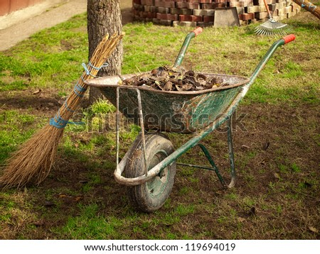 Retro broom and wheelbarrow full of leaves after cleaning. - stock photo