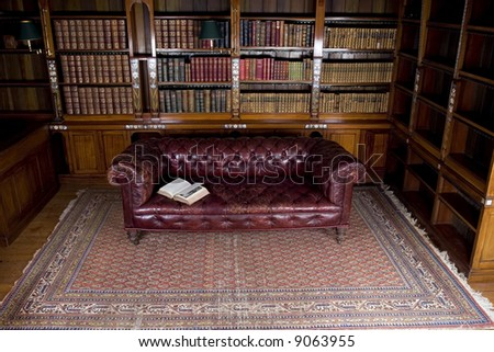 Retro brown leather sofa with open book on it - stock photo