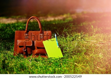 Retro brown  man leather bag and notebook in bright colorful summer grass in the park