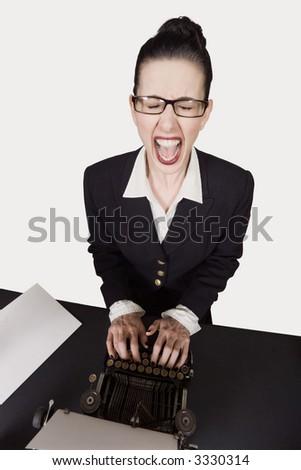 Retro business woman at vintage typewriter screaming - stock photo