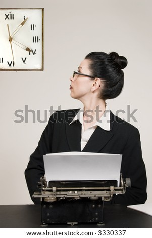 Retro business woman with vintage typewriter looking at wall clock - stock photo