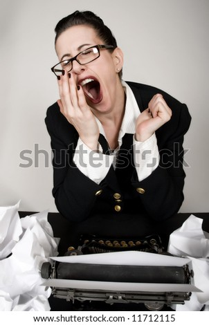 Retro business woman with vintage typewriter yawning - stock photo