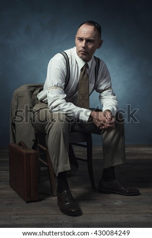 Retro 1940 businessman sitting on chair in room.