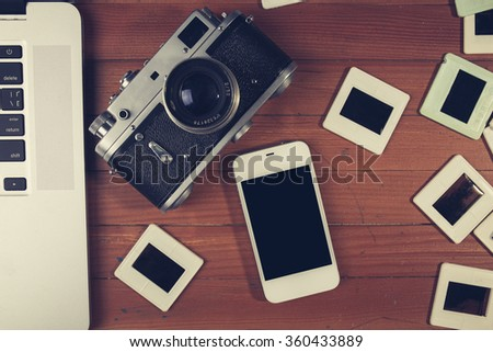 retro camera and some old photos on wooden table. Vintage look - stock photo