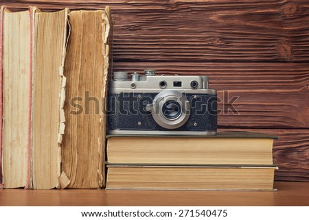 Retro Camera and Stack of Books Over Wooden Background - stock photo