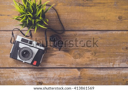 Retro camera on an old wooden table - stock photo