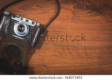retro camera on wooden background with type space