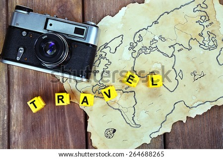Retro camera on world map with word Travel on wooden table background - stock photo