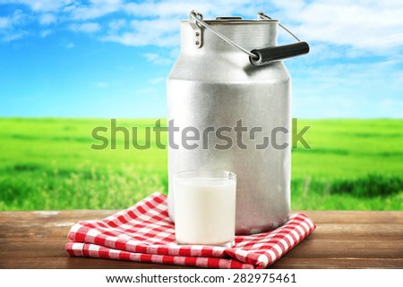 Retro can for milk and glass of milk on wooden table, on white background - stock photo