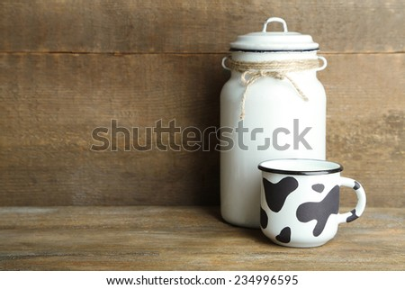 Retro can for milk and mug of milk on wooden table - stock photo