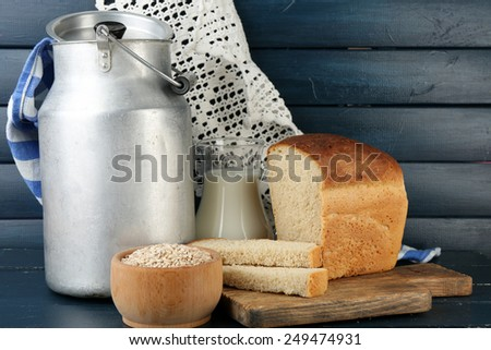 Retro can for milk with fresh bread and glass jug of milk on wooden background. Bio products concept - stock photo