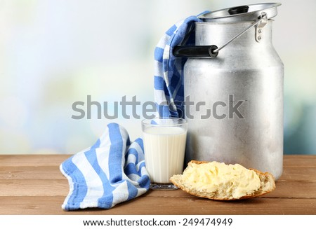 Retro can for milk with fresh bread and glass of milk on wooden table, on light background. Bio products concept - stock photo