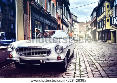 Retro car parked in old European city street - stock photo