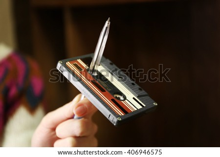 Retro cassette is twisted on pen against unfocused background - stock photo