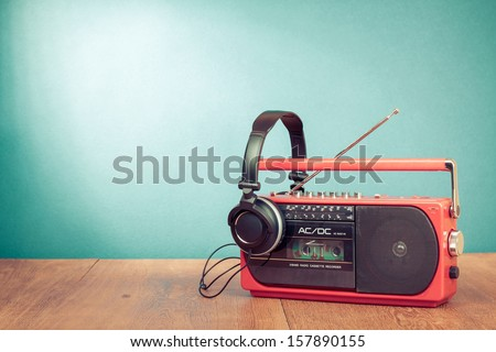 Retro cassette player and phones in front mint green background - stock photo