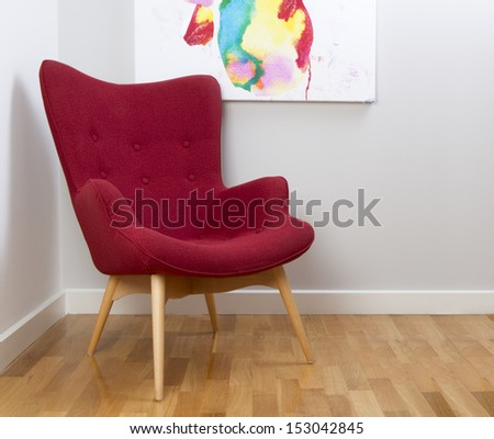 Retro chair on a grey wall background with part of a painting - stock photo