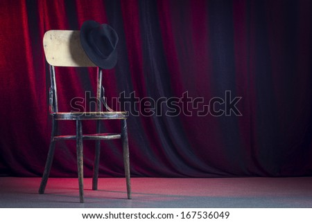Retro chair with a black felt hat against a red curtain.