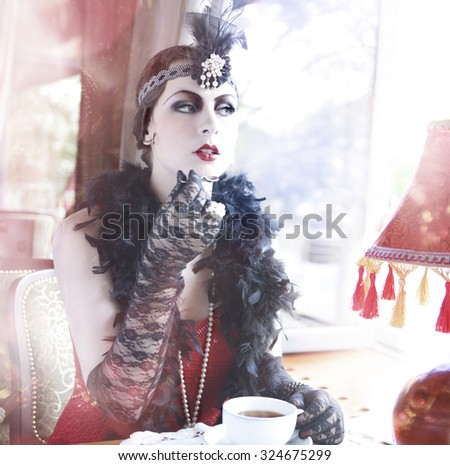 Retro  Charleston Woman Sitting with in a Restaurant Holding a Cup of Tea. The Portrait of The Beautiful Retro Woman Drinking Tea in the Cafe in Black Lace and Accessories in Style 1920 - 1930  - stock photo