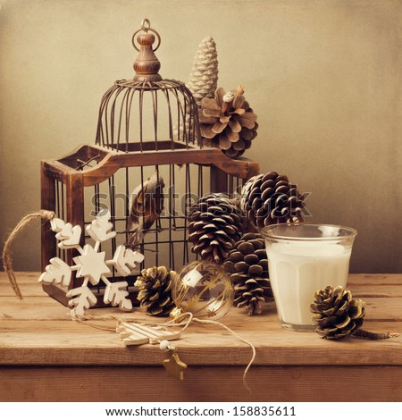 Retro Christmas composition with bird cage, glass of milk and decorations - stock photo
