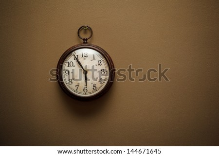 Retro clock on brown wall background - stock photo