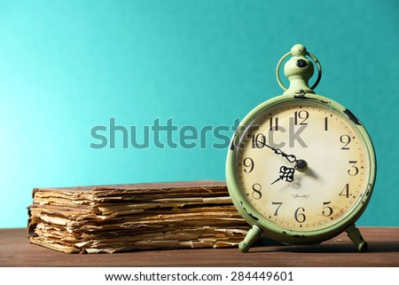 Retro clock with old book on table on green background - stock photo