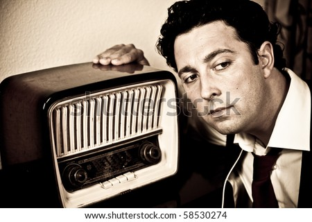 Retro - close up of dressed up man listening to old radio - stock photo