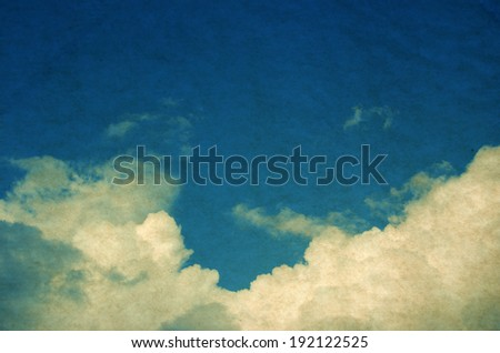 Retro cloudscape with vintage colors and a textured paper background. - stock photo