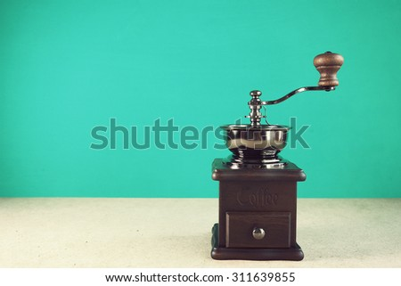 Retro coffee grinder on table front mint green background. Vintage effect. - stock photo