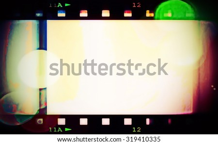 retro color film strip with spotlight background and texture - stock photo