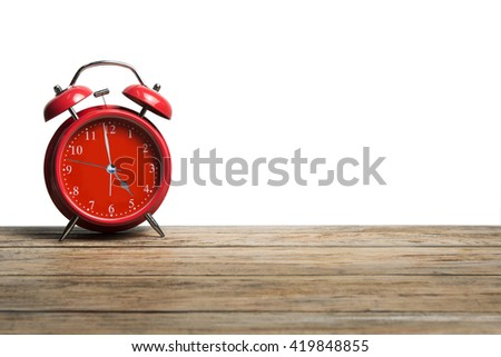 Retro colorful alarm clock on wooden board with white background. - stock photo