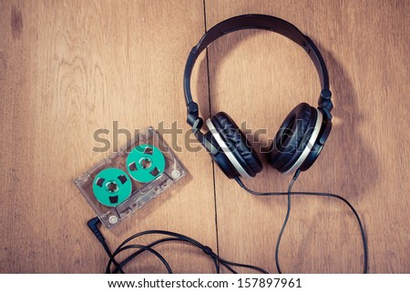 Retro compact cassette with rolls and headphones on wood - stock photo