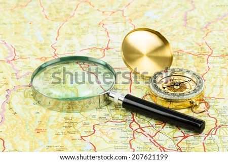 Retro compass and magnifier on a road map