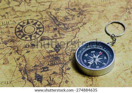 retro compass on old map - stock photo
