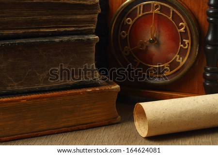 Retro composition with books, clock and paper on wooden background - stock photo