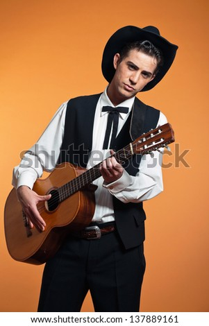 Retro country male guitar player wearing black suit and hat. Studio shot. - stock photo