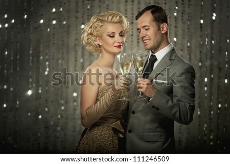 Retro couple with glasses of champagne - stock photo
