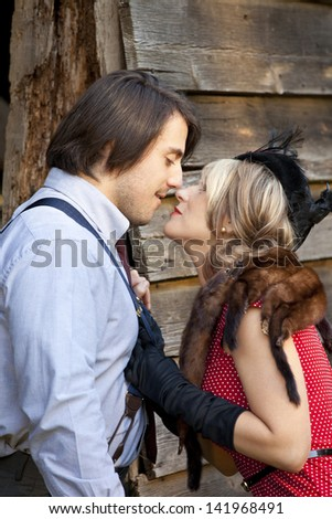 retro couple with woman grabbing his suspenders for kiss - stock photo
