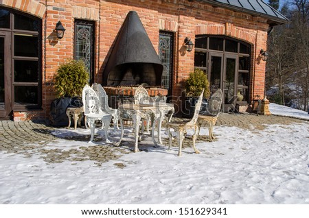 retro decorative outdoor table and chairs near restaurant fireplace building between snow in winter.  - stock photo