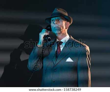 Retro detective man calling with vintage telephone at night in office. Lit by light through venetian blinds.