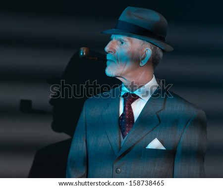 Retro detective man smoking pipe at night in office. Lit by light through venetian blinds.