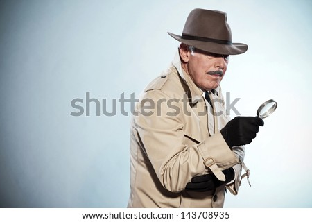 Retro detective man with mustache and hat. Holding magnifying glass. Studio shot. - stock photo