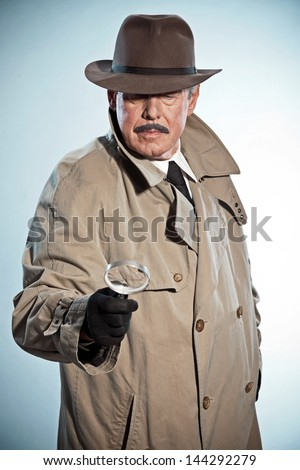 Retro detective with mustache and hat. Looking through magnifying glass. Studio shot. - stock photo