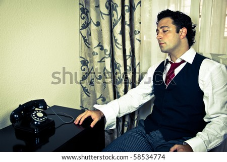 Retro - dressed up handsome man looking at an old telephone
