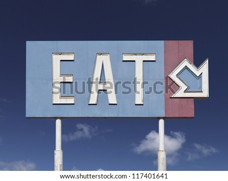 Retro eat arrow sign with blue sky near historic route 66. - stock photo