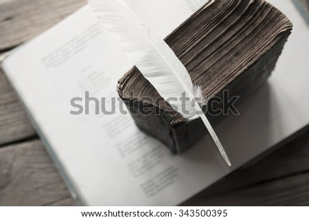 Retro education concept. Old book, book of poems and a feather. Toned photo - stock photo