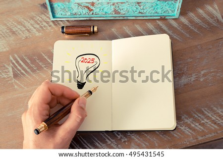 Retro effect and toned image of a woman drawing a lighting bulb with fountain pen on a notebook. Year 2025 symbol for bright idea and business concept, copy space available for text